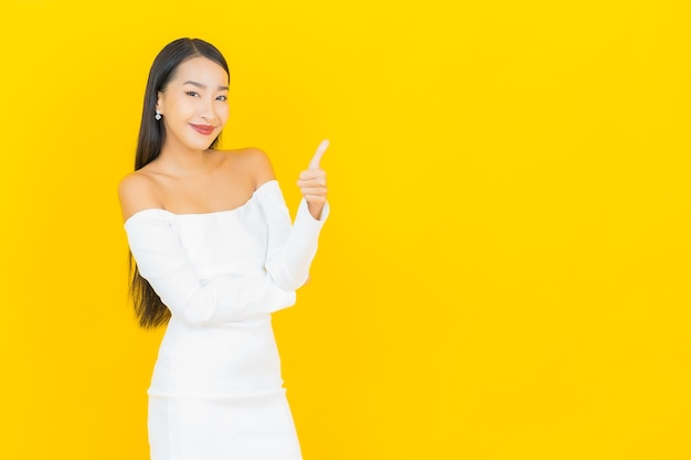 笑顔と黄色の壁に白いドレスで親指をあきらめて美しい若いビジネスアジアの女性の肖像画