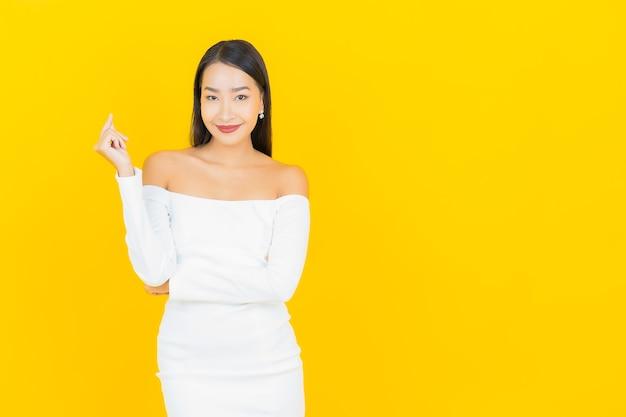 Портрет красивой молодой деловой азиатской женщины, улыбающейся с белым платьем на желтой стене