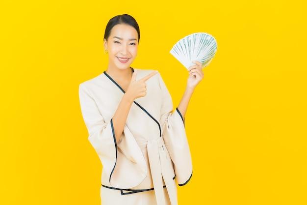 노란색 벽에 현금 돈과 돼지 저금통을 많이 가진 아름 다운 젊은 비즈니스 아시아 여자의 초상화