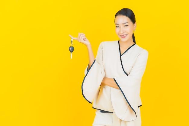 黄色の壁に車のキーを持つ美しい若いビジネスアジアの女性の肖像画