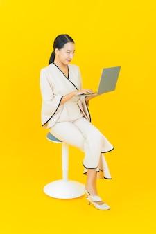 黄色の壁にコンピューターのラップトップを持つ美しい若いビジネスアジアの女性の肖像画