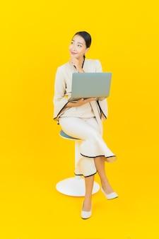 Портрет женщины красивого молодого дела азиатской с компьтер-книжкой компьютера на желтой стене