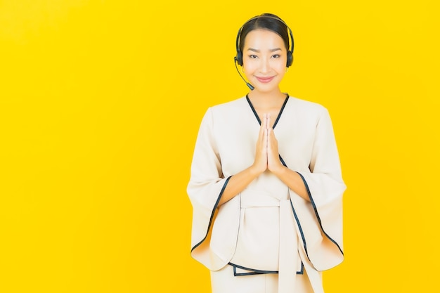 노란색 벽에 콜 센터 고객 관리를위한 헤드셋과 아름다운 젊은 비즈니스 아시아 여자의 초상화