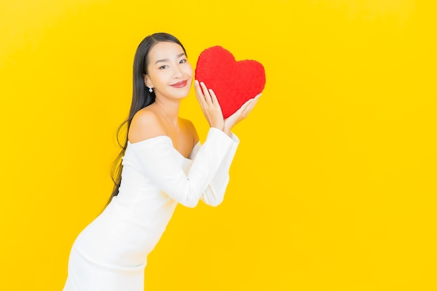 Портрет красивой молодой деловой азиатской женщины с подушкой в форме сердца на стене желтого цвета