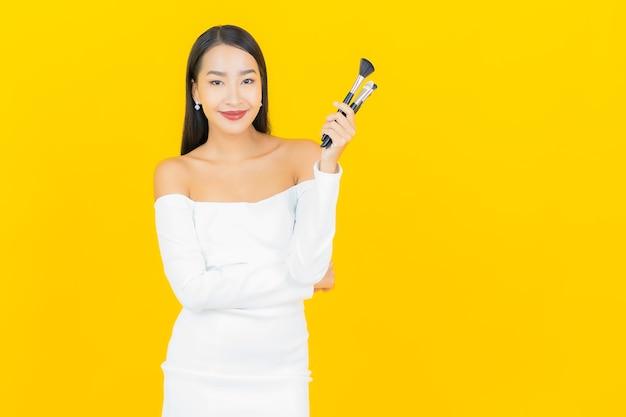 黄色の壁に化粧ブラシを作る美しい若いビジネスアジアの女性の肖像画