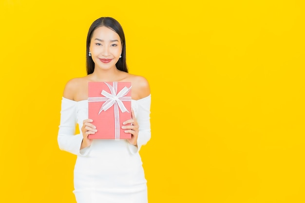 黄色の壁に赤いギフトボックスを持つ美しい若いビジネスアジアの女性の肖像画