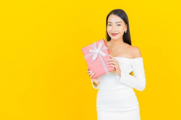 노란색 벽에 빨간색 선물 상자와 아름 다운 젊은 비즈니스 아시아 여자의 초상화