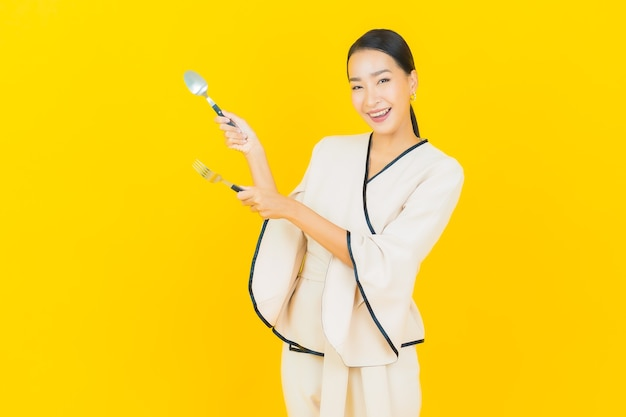 黄色の壁に食べ物を食べる準備ができてスプーンとフォークで美しい若いビジネスアジアの女性の肖像画