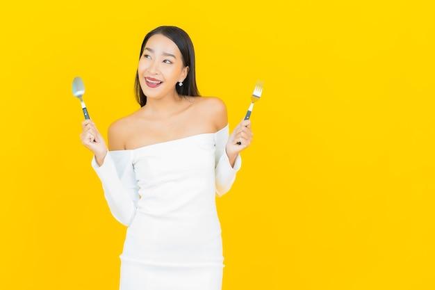 Портрет красивой молодой деловой азиатской женщины с ложкой и вилкой, готовой съесть еду на желтой стене