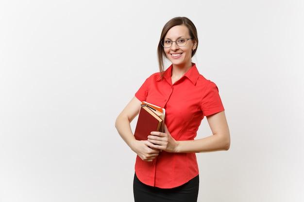 Портрет красивой молодой женщины учителя бизнеса в красной рубашке, черной юбке и очках, держа книги в руках, изолированных на белом фоне. образование или преподавание в концепции университета средней школы