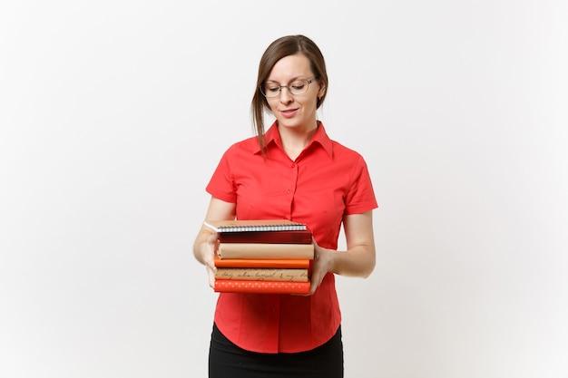흰색 배경에 격리된 손에 책을 들고 빨간 셔츠, 검은색 치마, 안경을 쓴 아름다운 젊은 비즈니스 교사 여성의 초상화. 고등학교 대학 개념의 교육 또는 교육