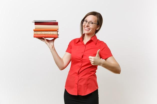 赤いシャツ、黒いスカート、白い背景で隔離の手で本を保持しているメガネの美しい若いビジネス教師の女性の肖像画。高校大学の概念における教育または教育
