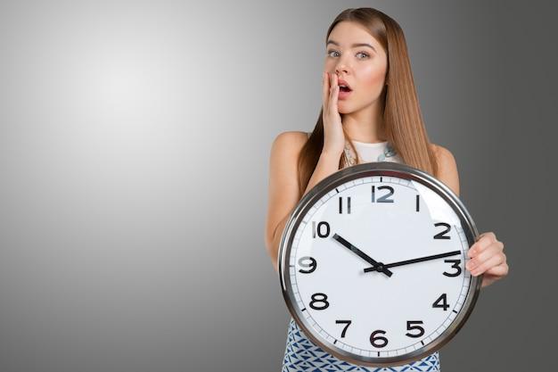 Портрет красивой молодой бизнес женщина держит в руках часы