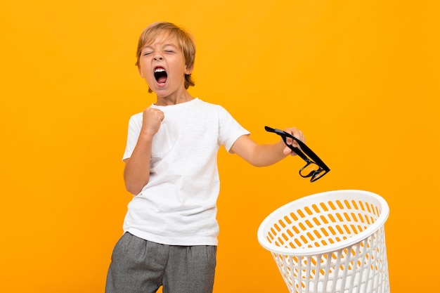 Портрет красивого молодого кавказского мальчика в белой футболке и серых брюках улыбается и отбрасывает очки