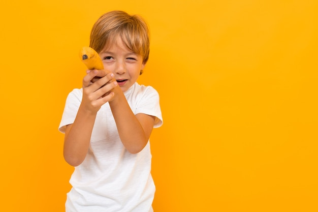 Портрет красивого молодого кавказского мальчика в белой футболке и серых брюках улыбается