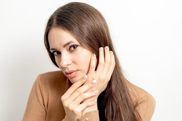 Портрет красивой молодой кавказской брюнетки с касанием ее волос ухоженными пальцами на белой стене