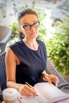 美しい若い白人ビジネスウーマンの肖像画は、カフェで眼鏡をかけているノートにメモを作成します