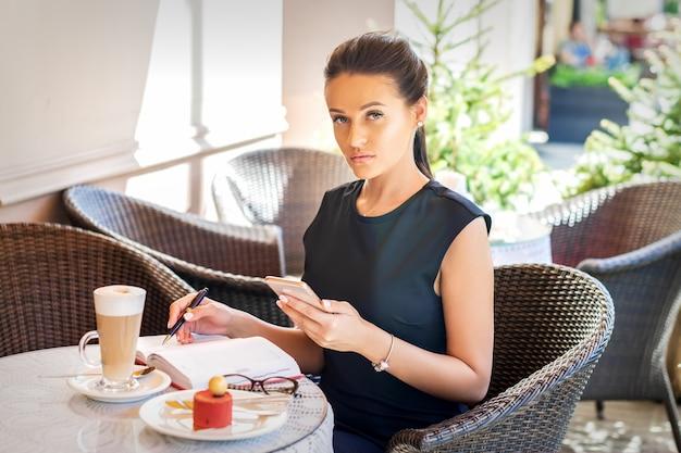 カフェに座っている携帯電話で美しい若い白人実業家の肖像画