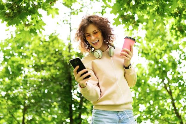 Портрет красивой молодой кавказской женщины гуляет в парке и пьет кофе