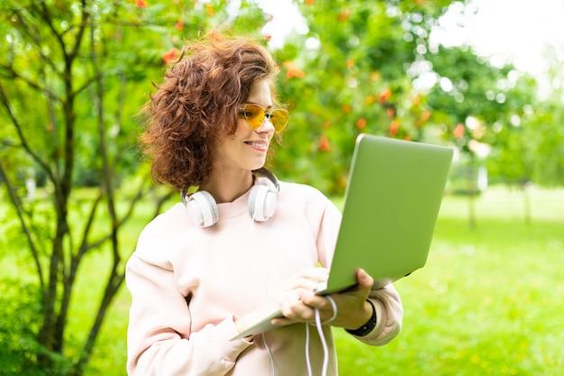 Портрет красивой молодой кавказской женщины гуляет в парке и работает с ноутбуком