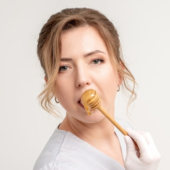 나무로되는 숟가락으로 꿀을 먹는 아름 다운 젊은 백인 여자의 초상화