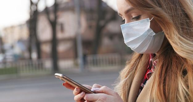 屋外の彼女のスマートフォンを使用して医療マスクで美しい若い白人女性の肖像画。通りでパンデミック中に電話でかわいい女の子のテキストメッセージ。パンデミックの概念、コロナウイルスの流行。
