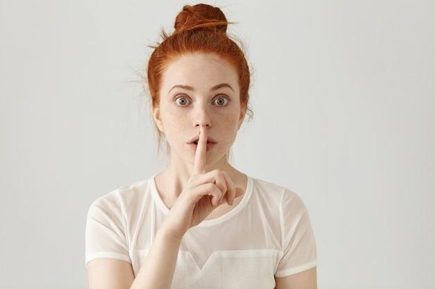 唇に人差し指を保持している生姜髪のお団子と美しい若い白人女性のポートレート