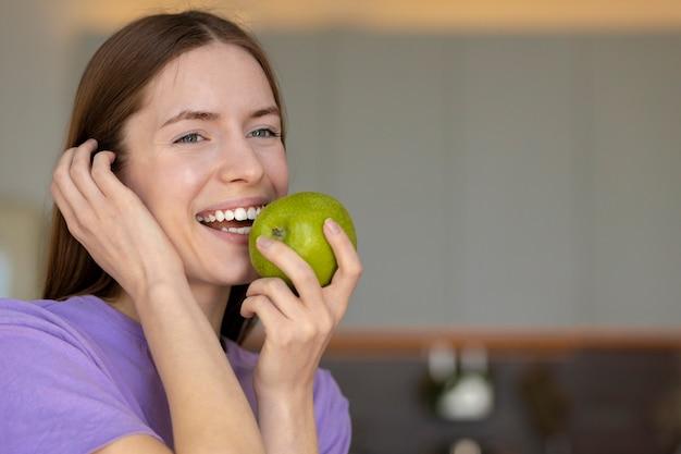 笑顔と青リンゴを食べる白い歯を持つ美しい若い白人女性の肖像画、健康的なライフスタイル、コピースペース