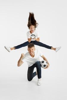 美しい若いカップルのサッカーやサッカーファンの肖像画。顔の表情、人間の感情、広告、スポーツのコンセプト。女性と男性がジャンプし、叫び、楽しんでいます。