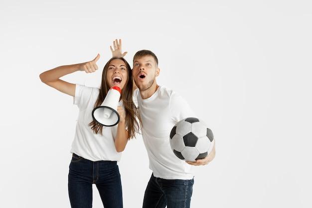 白いスペースに美しい若いカップルのサッカーやサッカーファンの肖像画。顔の表情、人間の感情、広告、スポーツの概念