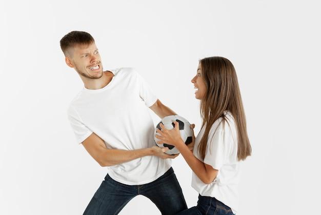 白いスタジオの背景に美しい若いカップルのサッカーやサッカーファンの肖像画。顔の表情、人間の感情、広告、スポーツのコンセプト。ジャンプ、叫び、楽しんでいる女性と男性。