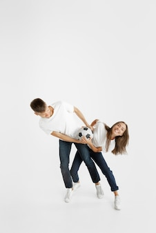흰색 스튜디오 배경에 아름 다운 젊은 부부 축구 또는 축구 팬의 초상화. 표정, 인간의 감정, 광고, 스포츠 개념. 여자와 남자 점프, 비명, 재미.