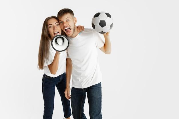 白いスタジオの壁に美しい若いカップルのサッカーやサッカーファンの肖像画