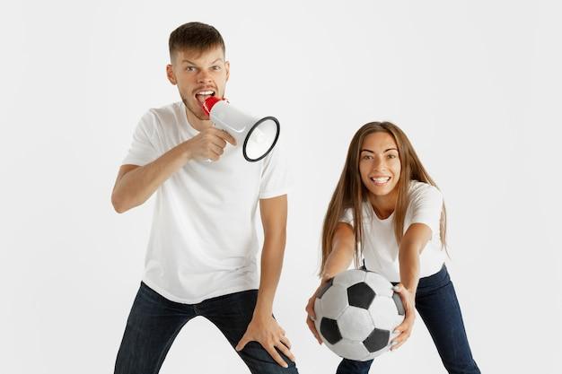白いスタジオで美しい若いカップルのサッカーやサッカーファンの肖像画
