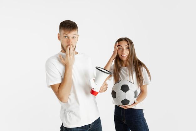 白い壁に美しい若いカップルのサッカーやサッカーファンの肖像画。顔の表情、人間の感情、広告、スポーツのコンセプト。女性と男性がジャンプし、叫び、楽しんでいます。