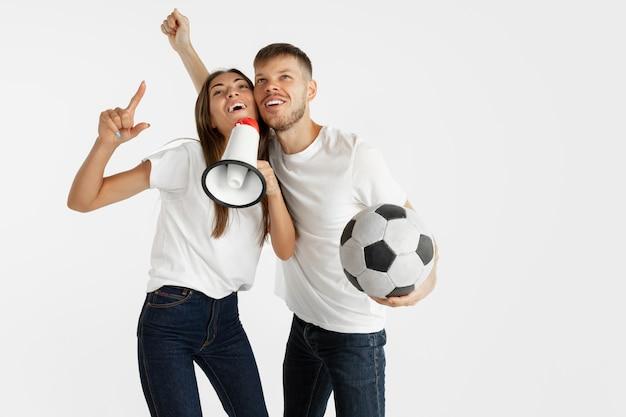 Портрет красивой молодой пары футбола или футбольных фанатов на белой стене. выражение лица, человеческие эмоции, реклама, спортивная концепция. женщина и мужчина прыгают, кричат, веселятся.