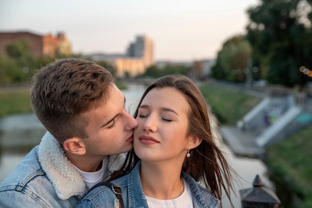 美しい若いカップルの肖像画。男は彼の最愛の人に優しくキスします。幸せな女の子は目を閉じた。街のロマンチックなデート。