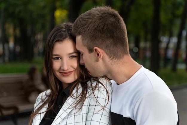 Портрет красивой молодой пары в парке. парень нежно касается носом щеки девушки.