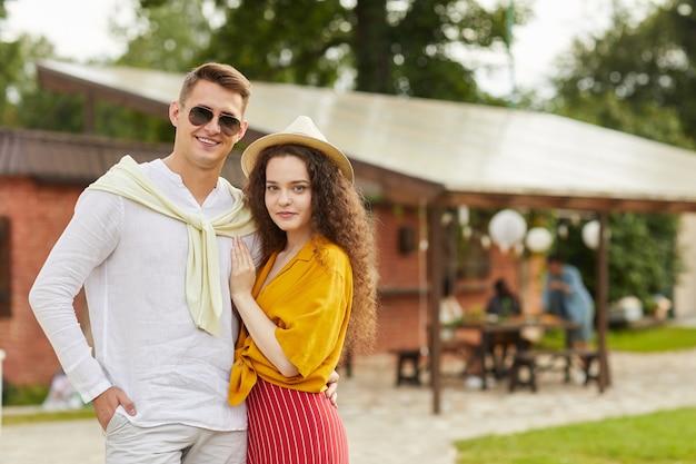 夏の屋外リゾートのコテージでポーズをとって美しい若いカップルの肖像画