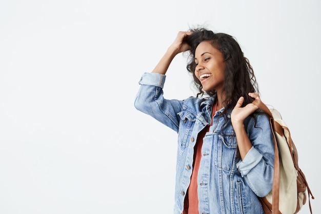 カジュアルな赤いtシャツとデニムジャケットを身に着けている彼女の肩にバックパックを楽しそうに微笑んでいるウェーブのかかった黒い髪を持つ美しい若い浅黒い女性の肖像画。気分が良いトレンディな流行に敏感な女性