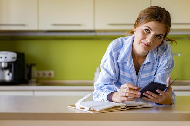 キッチンノルディックスタイルでポーズをとって美しい若い女性のプロの宇宙オーガナイザーの肖像画