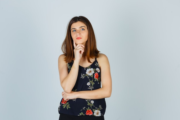 블라우스에 손에 턱을지지하는 아름 다운 젊은 여성의 초상화