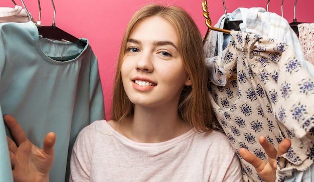 美しい少女の肖像画はドレス、分離された彼女のワードローブの中の女の子を選択します