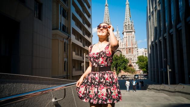 현대적이고 오래된 건물이 있는 오래된 도시를 걷고 있는 짧은 드레스를 입은 아름다운 소녀의 초상화. 여성 관광 관광 유럽 도시