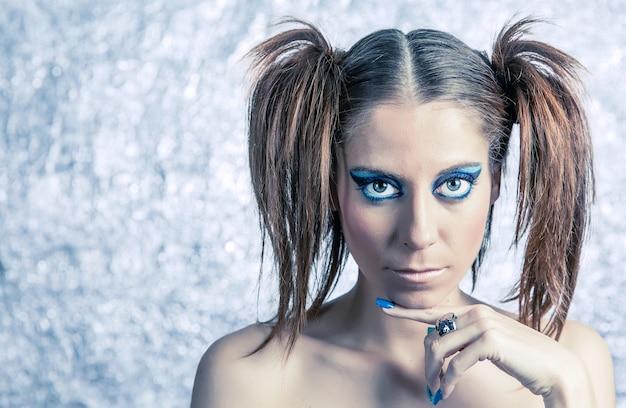 ぼやけた金属の背景の上にピグテール、明るい派手なメイク、青いマニキュアと美しい少女モデルの肖像画