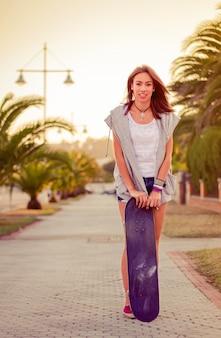 暑い夏の日に屋外でショートパンツとスケートボードを持つ美しい少女の肖像画。温かみのあるトーンエディション。