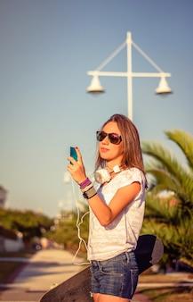 彼女のスマートフォンを屋外で見ているスケートボードとヘッドフォンを持つ美しい少女の肖像画。温かみのあるトーンエディション。