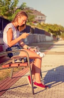 ベンチに座っている彼女のスマートフォンを見ているスケートボードとヘッドフォンを持つ美しい少女の肖像画。温かみのあるトーンエディション。