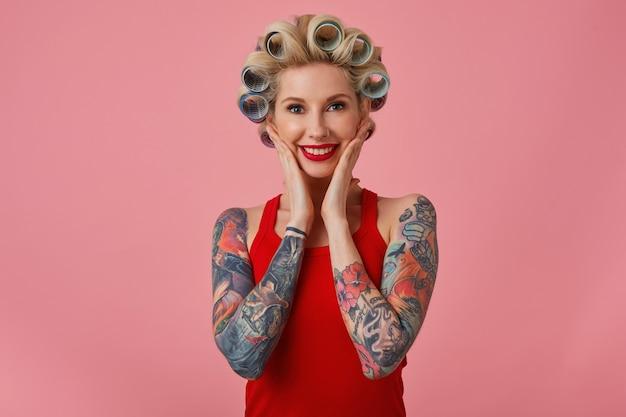 Портрет красивой молодой счастливой блондинки, держащей ладони на щеках и широко улыбающейся, позируя на розовом фоне, имея татуировки на руках и бигуди на голове
