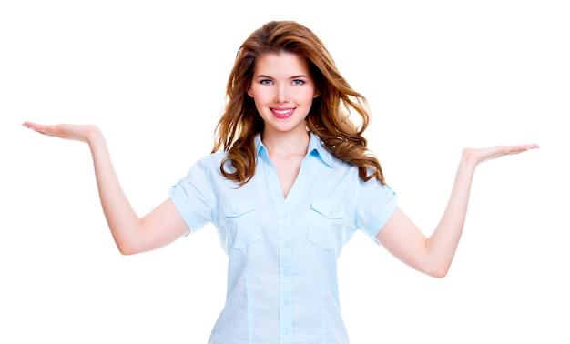 美しい若い幸せな女性の肖像画は手のひらに何かを保持します-孤立